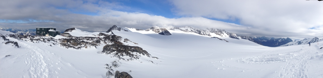 A 180 degree panorama.  From left, the Thomas Training Center where we live on the glacier, the glacier itself and ski trails in the middle, and a skier at the start of the trail to the far right.